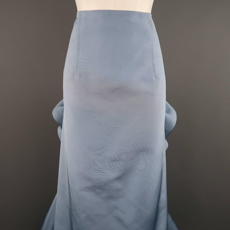 This stunning evening skirt by CAROLINA HERRERA comes in a light blue silk faille and features an A line pencil skirt style front, cascading side ruffles, and gathered ruffle back with peplum. Minor wear and discolorations shown in detail shots.
