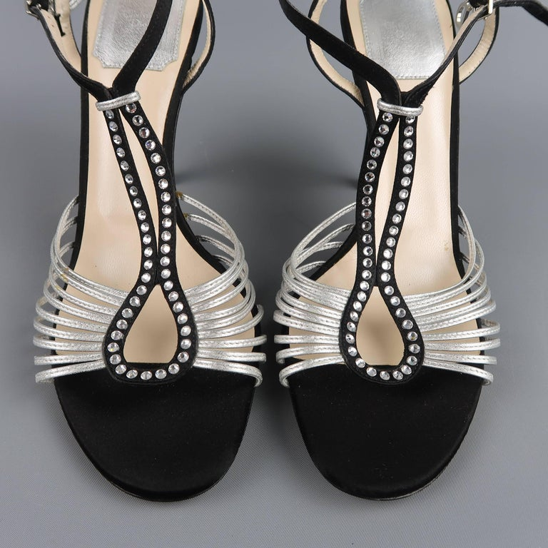 These fabulous CHRISTIAN DIOR evening sandals feature a black silk satin hoop T strap with rhinestones, covered stiletto heel, and metallic silver skinny strap details. Discolorations on silver strap and scuff on heel shown in detail shots. As-Is.