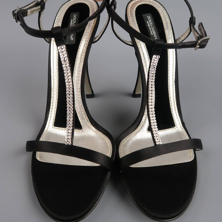These fabulous DOLCE & GABBANA evening sandals feature a black silk satin & silver metallic leather sole with velvet padding, silk covered stiletto heel, skinny toe strap, ankle harness, and rhinestone studded T strap. Made in Italy.   Good