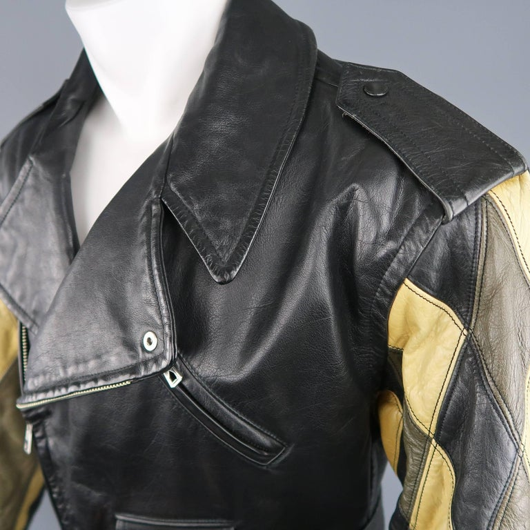 Vintage 1980's JEAN PAUL GAULTIER motorcycle style jacket comes in black structured leather and features a pointed collar lapel, asymmetrical zip closure, belted waist, zip pockets, signature back tab, and olive green and beige patchwork diamond