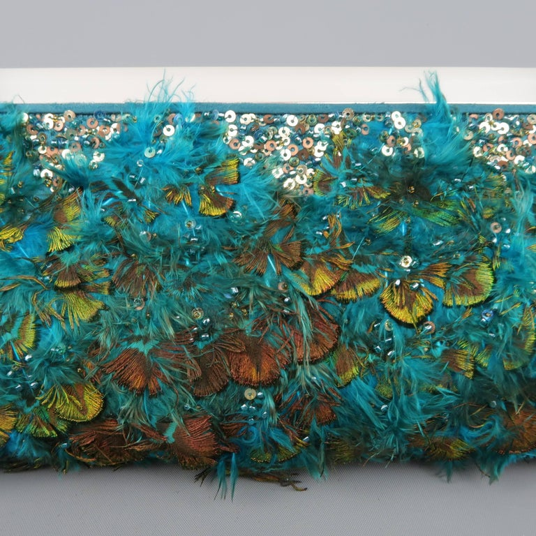 This fabulous Judith Leiber evening clutch comes in a vibrant teal green silk satin completely embellished with peacock feather and sequins with a matte lucite handle detailed with blue and white art deco style crystal adornments, optional silver