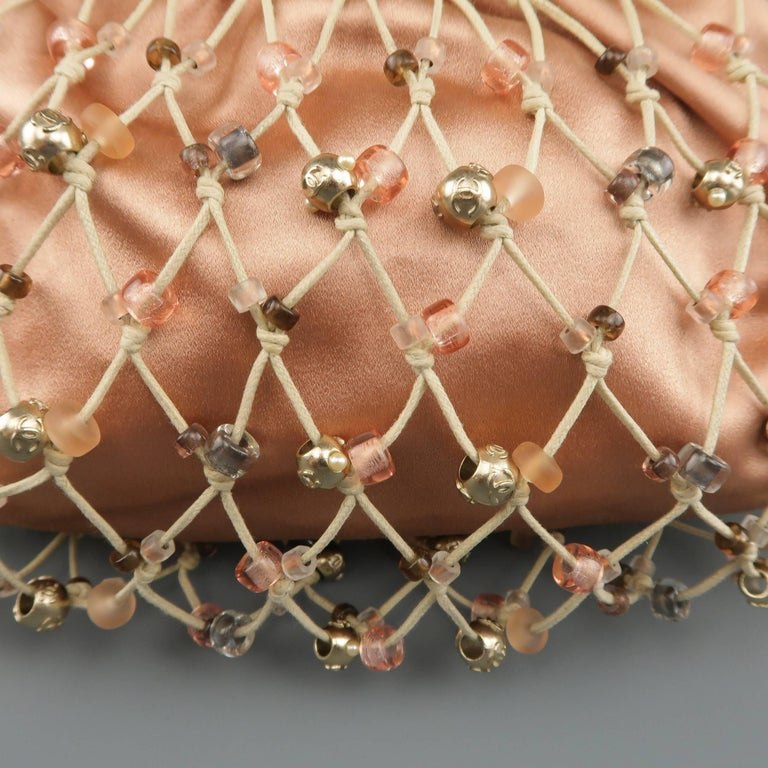 Rare archive Chanel purse features a salmon pink silk satin pouch with beaded beige fishnet mesh overlay and a thick  leather covered handle. Minor wear on handle and internal lining stains. As is. Made in France.   Excellent Pre-Owned