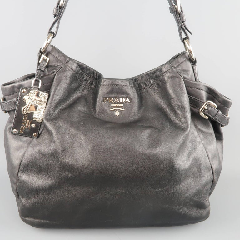 3ad22be42e Classic PRADA hobo shoulder bag comes in soft black leather and features a  silver tone metal