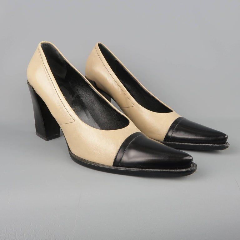PRADA pumps come in a taupe beige and black leather and feature a pointed cap toe and stacked chunky heel. Minor wear. Made in Italy.   Good Pre-Owned Condition. Marked: IT 40   Heel: 3 in.  SKU: 87208