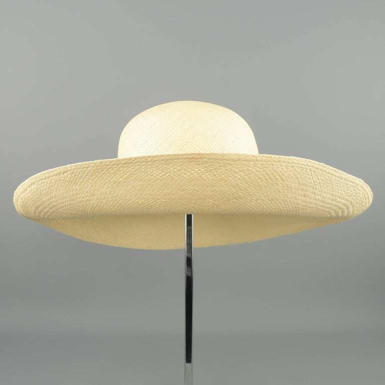 Vintage sun hat in light beige woven straw with a semi wide brim. Good Pre-Owned Condition.   Measurements:     Opening: 7 x 7.5 in.     Brim: 4 in.     Height: 4 in.