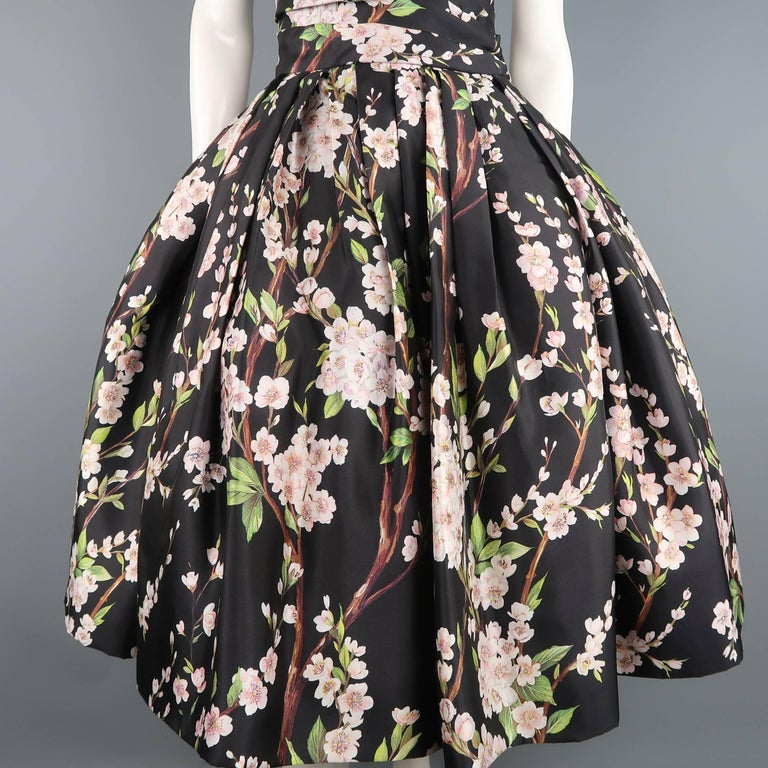 This gorgeous DOLCE & GABBANA cocktail dress comes in black silk twill with all over cherry blossom floral print and features an asymmetrical pleated fully boned bustier bodice with pointed sweetheart line and midi length circle skirt with full