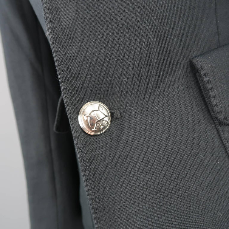 RALPH LAUREN blazer comes in a black cotton jersey and features a notch lapel with top stitching, double patch flap pockets, silver tone engraved buttons, faux button cuffs, and RL coat of arms metallic embroidered breast pocket.   Good Pre-Owned