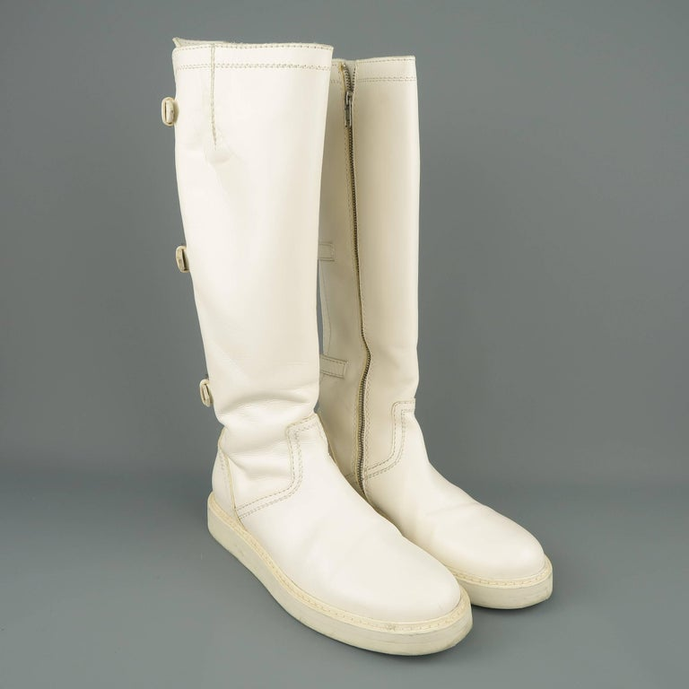 ANN DEMEULEMEESTER knee high boots come in off white leather with a round toe, thick rubber sole, buckle strapped back, and internal zip closure. Made in Italy.   Good Pre-Owned Condition. Marked: IT 41   Measurements:   Outsole: 12 x 4.5