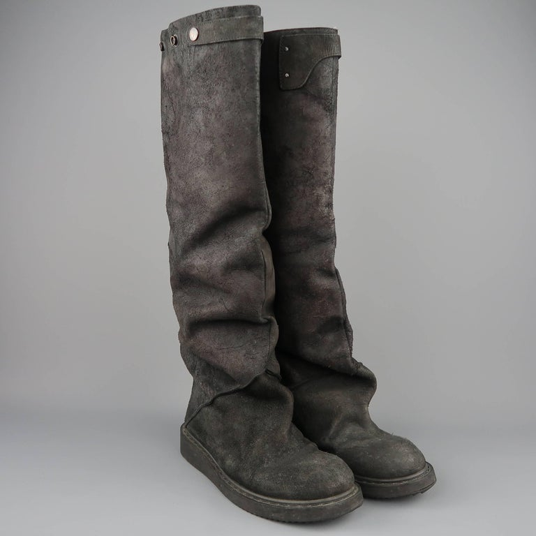 RICK OWENS knee high boots come in black sueded distressed leather with a round toe, thick sole, oversized slouchy construction, and back zip closure. Wear throughout. Made in Italy.   Good Pre-Owned Condition. Marked: IT 41   Measurements: