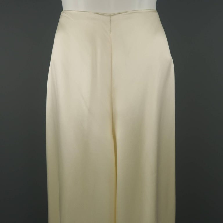 RALPH LAUREN COLLECTION dress pants come in light creamy beige silk blend satin with a minimalist deign, high rise, and extreme wide leg silhouette. Made in USA.   Good Pre-Owned Condition. Marked: 8   Measurements:   Waist: 27 in. Rise: 12.5