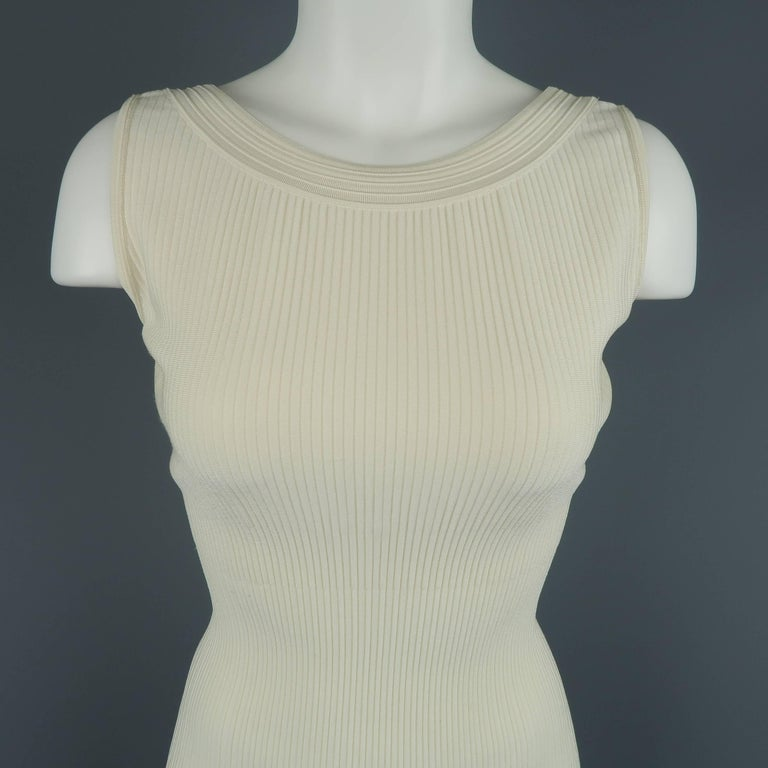 ALAIA bodycon dress comes in creamy beige ribbed stretch knit with a scoop neck and deep V back. Made in Italy.   Excellent Pre-Owned Condition. Marked: XS   Measurements:   Shoulder: 12.5 in. Bust: 36 in. Waist: 22 in. Hip: 26 in. Length: 39 in.