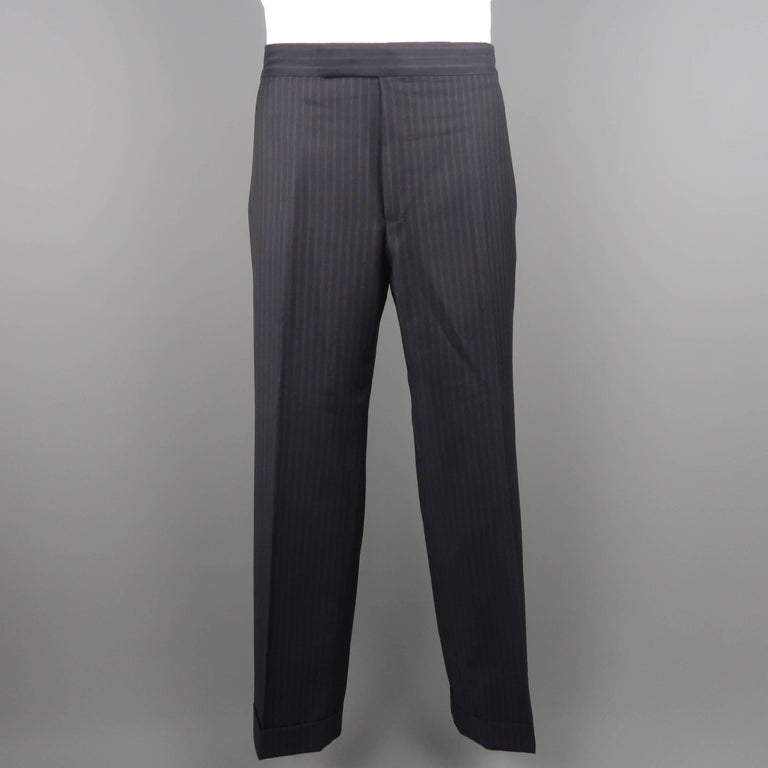 Two piece Tom Ford suit comes in black pinstriped wool twill and includes a single breasted, two button sport coat with notch lapel, triple flap pockets, and functional button cuffs with matching flat front, cuffed dress pants.  Made in Italy.