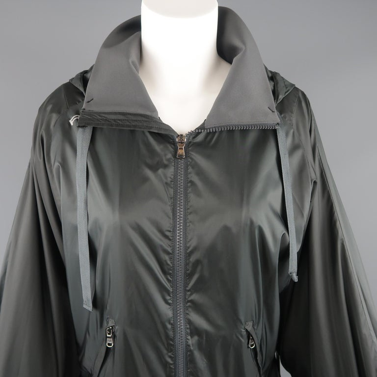 RLX by RALPH LAUREN hooded sport jacket comes in light weight charcoal nylon with a zip up front, nigh collar, slanted zip pockets, batwing sleeves with extended thumb hole cuffs, and drawstring hood.   Excellent Pre-Owned Condition. Marked: S