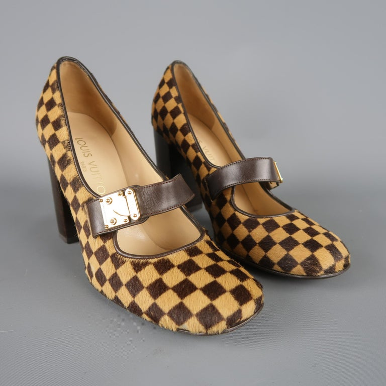Fabulous statement pumps by Louis Vuitton. A retro inspired style in gorgeous tan and chocolate brown Damier checkered pony hair featuring a rounded square toe, thick chocolate brown leather Mary Jane strap with gold tone decorative LV engraved