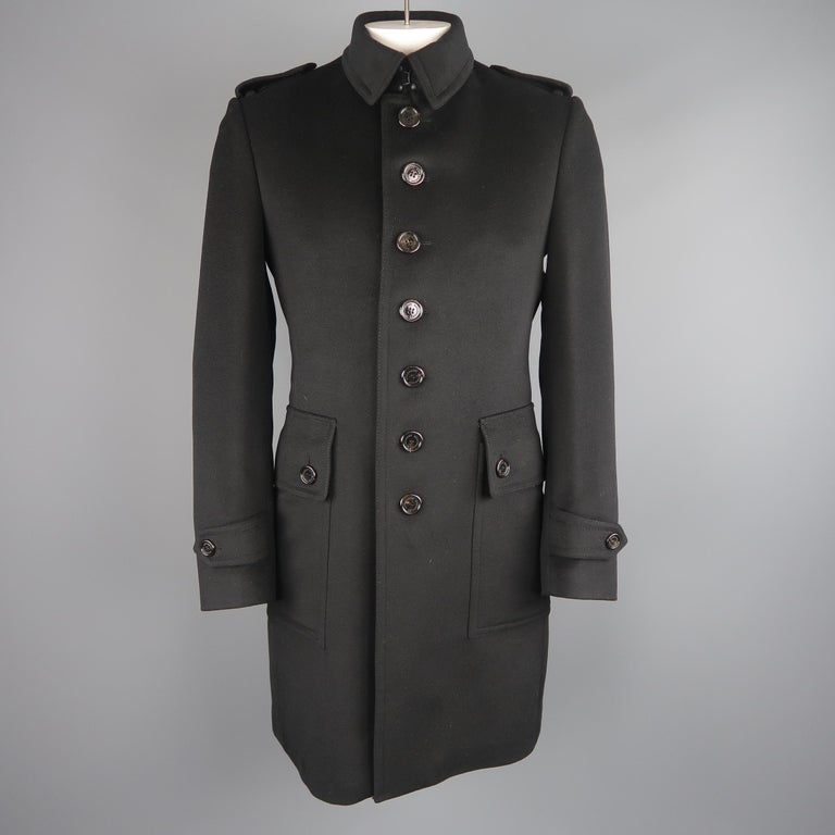 Burberry London single breasted trench coat comes in a soft wool cashmere blend fleece with a pointed collar with hook eye, epaulets, button up front, patch flap pockets, belted waist, and tab cuffs. Minor imperfection in fabric on left pocket.