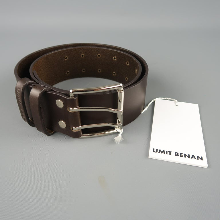 UMIT BENAN belt features a thick dark brown leather strap with a silver tone double prong buckle. Made in Italy.   New with Tags. Marked: 84   Length: 40 in. Width: 1.75 in. Fits: 26-35 in.