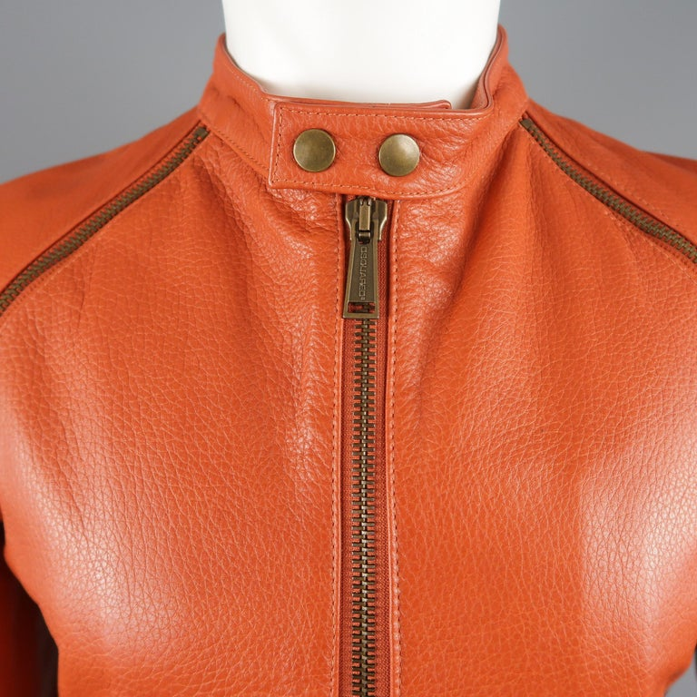 DSQUARED2 biker jacket comes in orange textured leather with a band snap over collar, double zip up front, gathered side panels, and antique gold tone zip sleeves. Minor wear shown in detail shots. Made in Italy.   Good Pre-Owned Condition. Marked:
