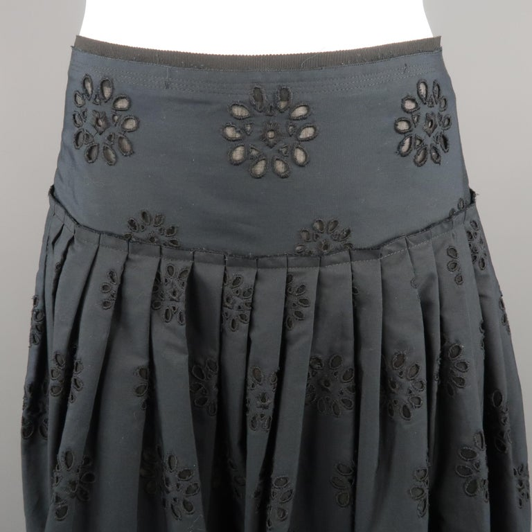 PRADA A-line skirt in a navy tone, cotton material, featuring eyelet embroidery and pleats on the top. Made in Italy.   Excellent Pre-Owned Condition. Marked: 38 IT   Measurements:   Waist: 28 in. Hip: 40 in. Length: 27.5 in.