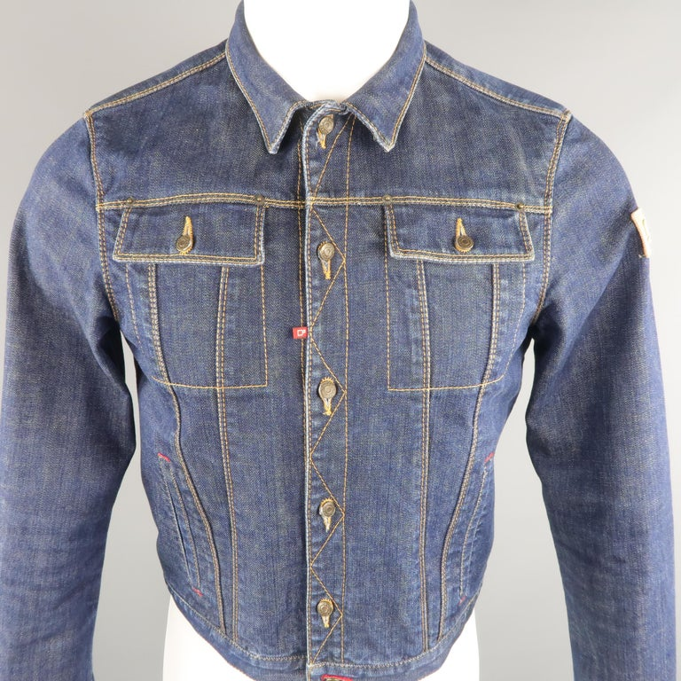 DSQUARED2 cropped jacket come in indigo denim, contrast stitches, patch flap pockets and lateral patch label. Made in Italy.   Excellent Pre-Owned Condition. Marked: 48 IT   Measurements:   Shoulder: 15.5 in. Chest: 38 in. Sleeve: 27.5 in. Length: