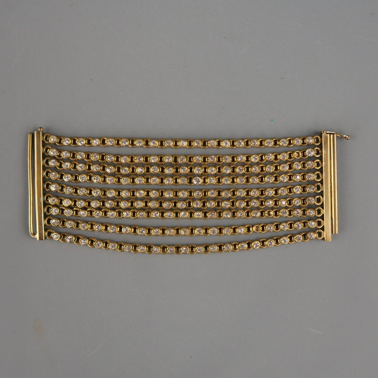Vintage Mid-century CHANEL cuff bracelet comes in antique gold tone bras and features nine rows of white rhinestone chain strands with rod clasp closure. Minor wear on closure and missing three stones.  Includes a Chanel dust bag.   Vintage