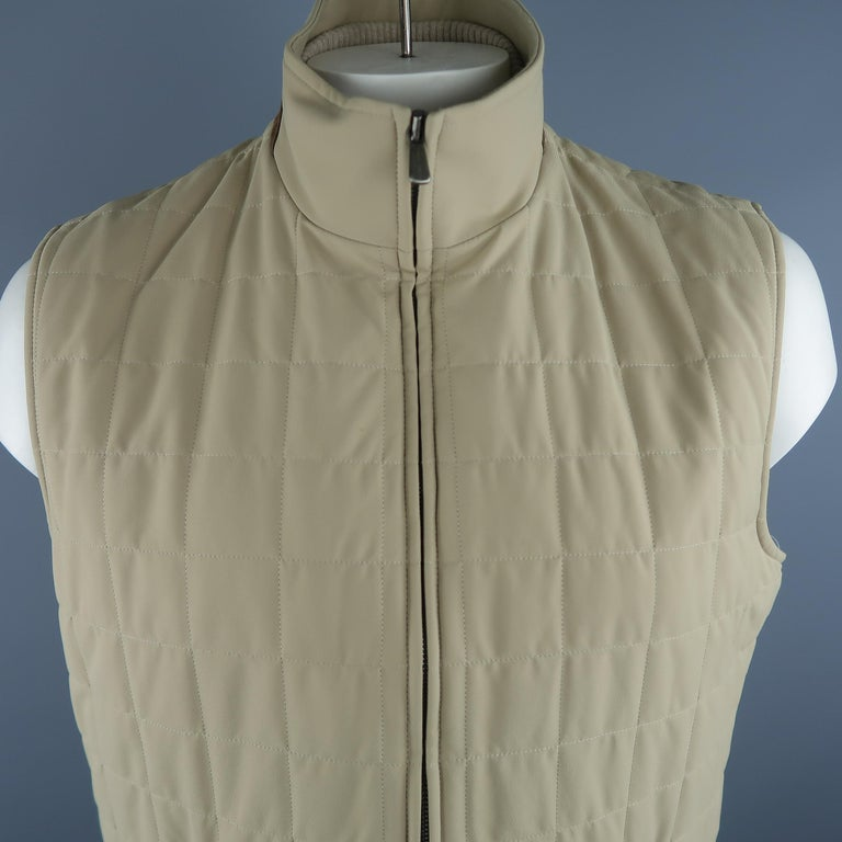 LORO PIANA vest comes in khaki quilted nylon material, suede trim on the collar, zip up and zip pockets. Made in Italy.   Excellent  Pre-Owned Condition. Marked: XL IT   Measurements:   Shoulder: 18 in. Chest: 48 in. Length: 27.5 in.