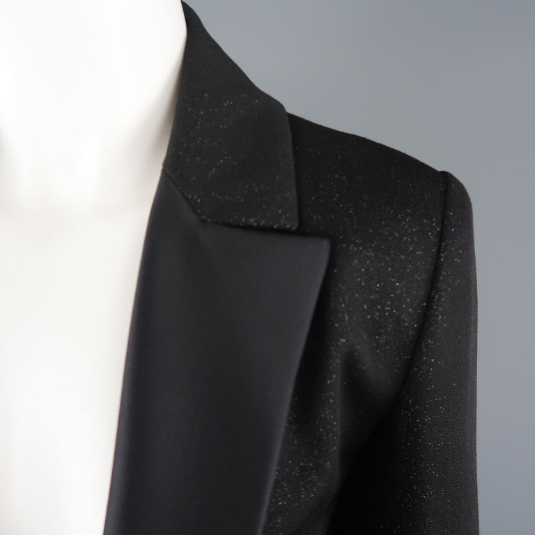CHANEL tuxedo style jacket comes in a black wool blend twill with an all over glitter sheen and features a half silk satin peak lapel, single button front with rhinestone enamel chain closure, and functional button cuffs. Made in France.   Excellent