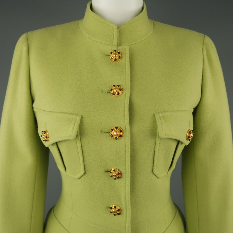 Vintage circa Fall Winter 1996 CHANEL BOUTIQUE military style jacket comes in light pistachio green wool with a stand up Nehru collar, four patch flap pockets, six button front, silk Camellia lining with chain weight, functional button cuffs and