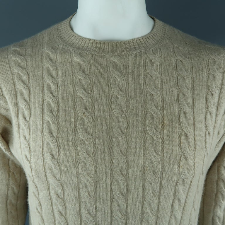 LORO PIANA sweater come in cashmere in a khaki tone, cable knit, with a crewneck and ribbed cuffs and waistband. Made in Italy.   Excellent Pre-Owned Condition. Marked: 50 IT   Measurements:   Shoulder: 17.5  in. Chest: 48  in. Sleeve: 26.5
