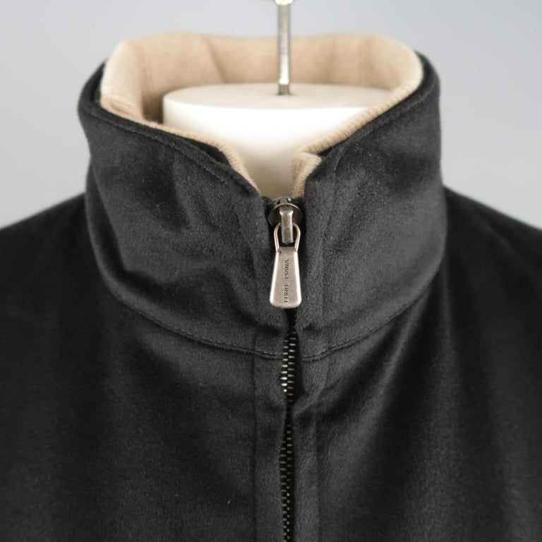 LORO PIANA Storm System jacket comes in black cashmere with a high, detachable ribbed knit lined collar, double zip front, slanted zip pockets, and tan suede trim. Made In Italy.   New without Tags. Retails: $2,695.00. Marked: XL   Measurements: