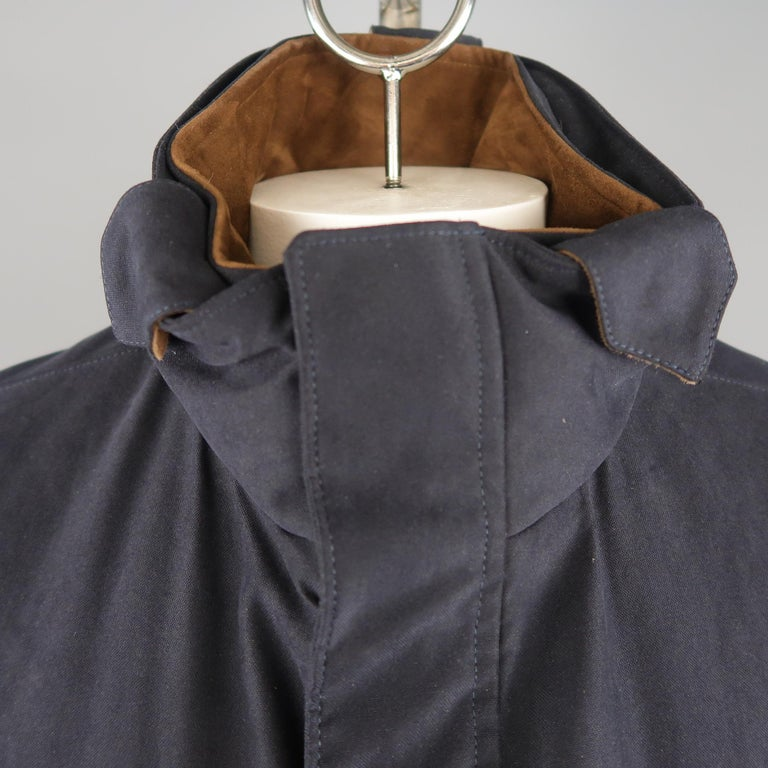 LORO PIANA Storm System jacket comes in navy fabric with a high collar, double zip  front with snap placket, slanted zip pockets, flap pockets, detachable inner collar, and brown suede trim. Made In Italy.   New without Tags. Retails: