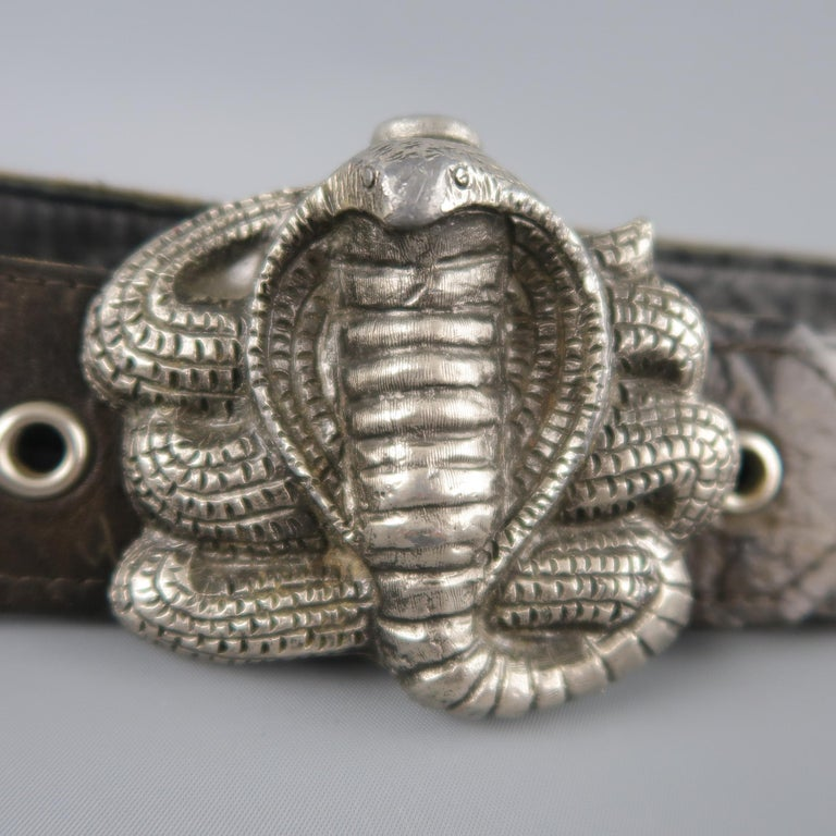 Vintage IN-STYLE 1979 belt features a black leather silver tone studded strap with antiqued silver tone metal cobra buckle.   Good Pre-Owned Condition. Marked: R 2002   Length: 36.5 in. Width: 1.95 in. Fits: 30-34 in. Buckle: 3.5 x 2.75 in.