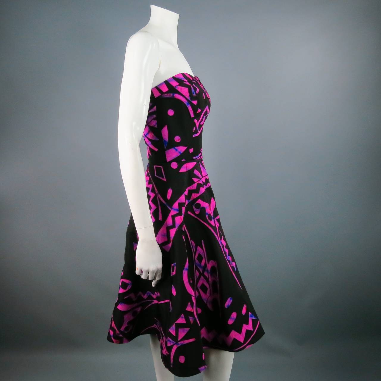 Fabulous strapless cocktail dress by OSCAR DE LA RENTA. A very unique style for Spring/Summer in a classic fitted bodice,including built in bustier, with flare skirt in a black silk material with fuchsia and blue tie die tribal print applique.Made