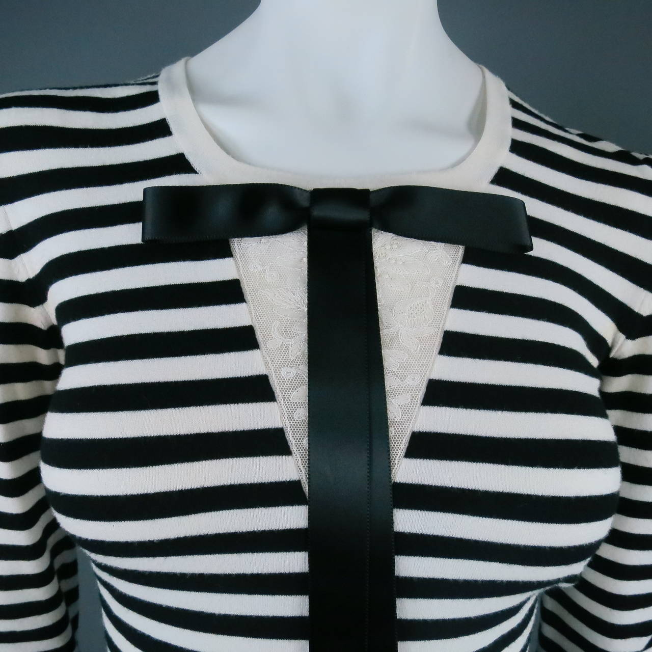 Gorgeous black and white striped sweater by CHANEL. A nautical style with a scoop neck, featuring a white lace applique panel under the neckline with a detachable black ribbon bow. Made in France.