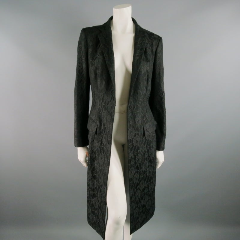 RICHARD TYLER COUTURE makes a gorgeous suit coat in a light/medium weight black wool, layered with black, floral lace. Single, sturdy snap a center front.  Notch lapel, dual flap pockets.  small slits on either cuff.  Single, long pleat in back is