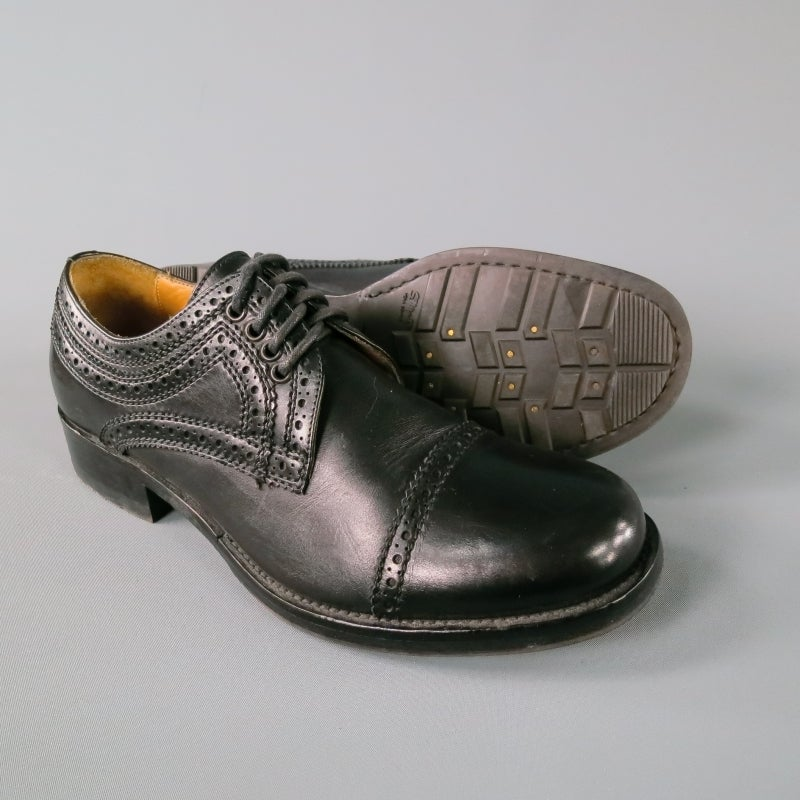 Stylish dress shoe by Alexander Mcqueen in black leather with perforated detailing.  Cap toe, wooden stack heel, 5 eyelet laces.  Made in Italy.   Excellent Pre Owned Condition.   Marked As:IT 41   Fits Like: US 8