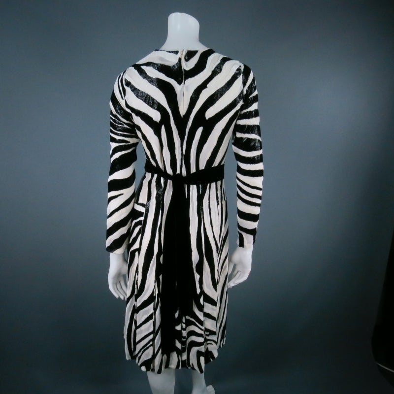 Stunning tinsel silk cocktail dress by TOM FORD. An ultra chic long sleeve style in black and white zebra print textured chiffon with sparkling lustre, featuring a crew neckline, pleated drop waist skirt, and velvet tie belt. A true show stopper for