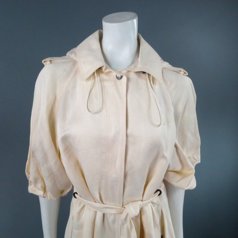 Fabulous cream trench coat by LANVIN. A classic staple with modern details, this piece features a pleated 3/4 sleeve with epaulets, collar with adjustable band zip off hood, hidden placket snap closures,  waist tie belt with grommets, and full skirt