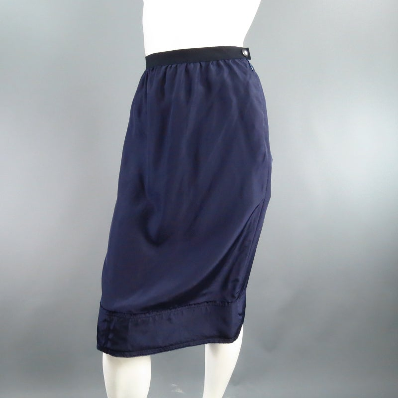 Lovely silk sheath skirt by LANVIN. A classic style in semi matte navy satin featuring a ribbon waist band with gathering and structures raw edge band hem. Circa 2008. Made in France.