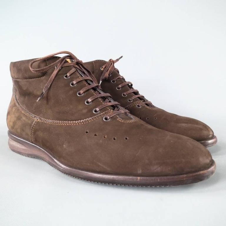 John Lobb Boots consists of suede material in a brown color tone. Designed in a Nubuck style, contrast stitching can be seen throughout vamp and back of heel. Dark brass eyelets are featured along vamp with brown color laces. Leather lining and