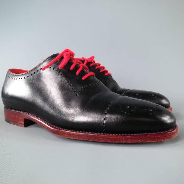 KITON Lace Up Shoe consists of leather material in a black color tone. Designed with a round-toe front, wing-tip detail, perforated accents toward vamp section and contrast red laces. Tone-on-tone stitching can be seen around edges with red leather