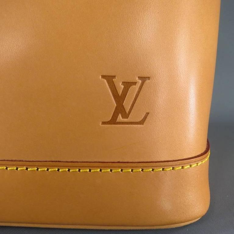 This ultra rare limited edition ALMA PM by LOUIS VUITTON comes in all natural Vacchetta patina leather and features a structured taper shape with rectangular base, double top handles with gold tone hardware, zip closure with LV lock and keys, and