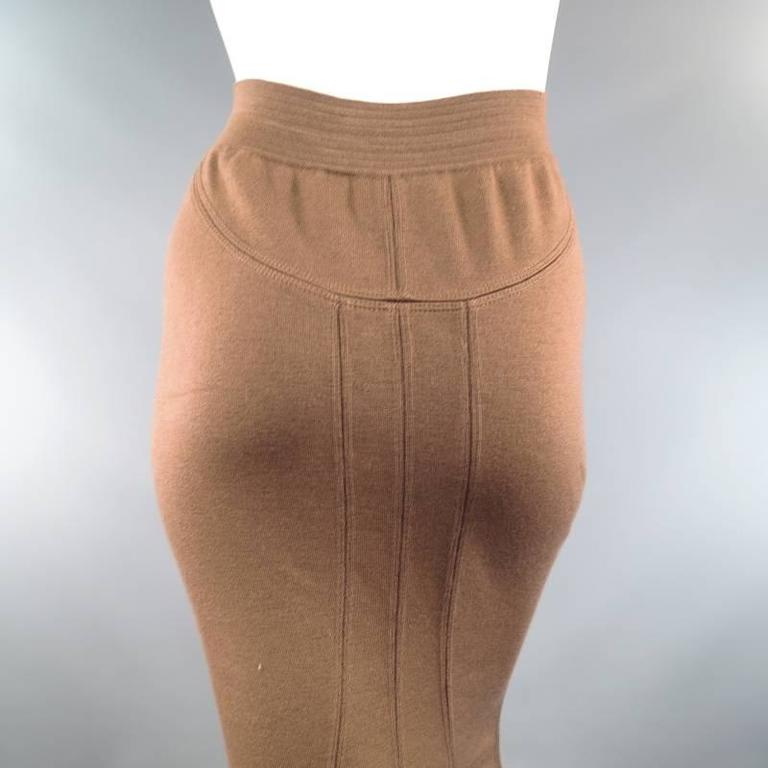This vintage midi pencil skirt from ALAIA comes in a gorgeous light tan taupe brown wool blend stretch knit and features a thick ribbed waistband, slinky bodycon fitted silhouette, and panel constructed back with fishtail hem. This vintage piece