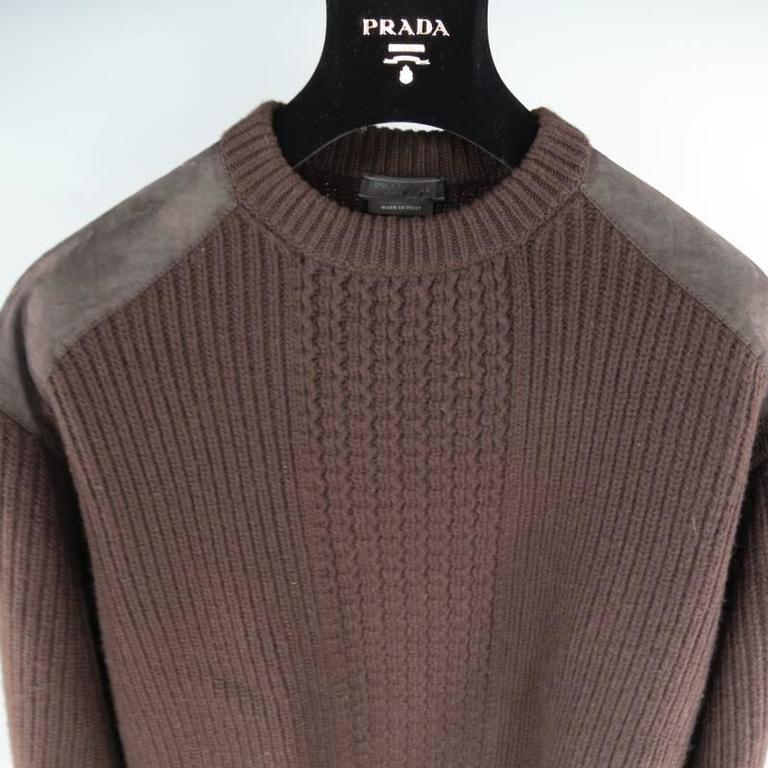 Prada Sweater consists of wool material in a brown color tone. Designed with a crew-neck collar, suede shoulder panels and tone-on-tone stitching throughout suede. Detailed with a woven mid-section, stripe ribbed pattern and blousen hem. Made in