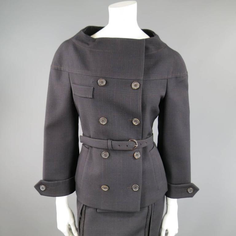 This fabulous 1960's inspired PRADA suit includes a jacket in a dark brown and navy blue plaid wool and features a button up double breasted closure, double side pockets , belted waist, sleeve epaulets, and high curved neckline with a matching raw