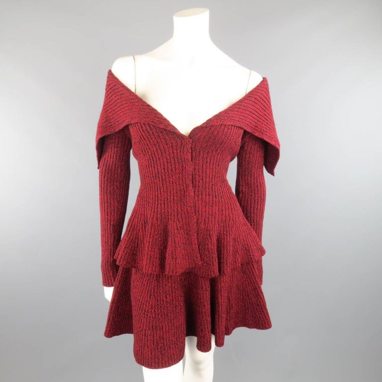 ALEXANDER MCQUEEN knitwear set includes comes in a burgundy, red, and black Heathered wool knit and includes a large, fold over shawl collar, hidden snap closure, and peplum waist cardigan jacket and matching ruffled mini skirt. Made in Italy.