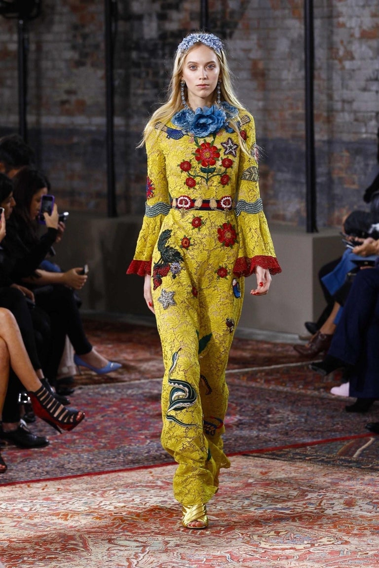 This fabulous Gucci Cruise 2016 Collection statement gown / dress comes in chartreuse yellow lace and features a round neck with detachable blue flower brooch, symmetrical blue bird and floral patches, bell sleeves with metallic red lace trim,