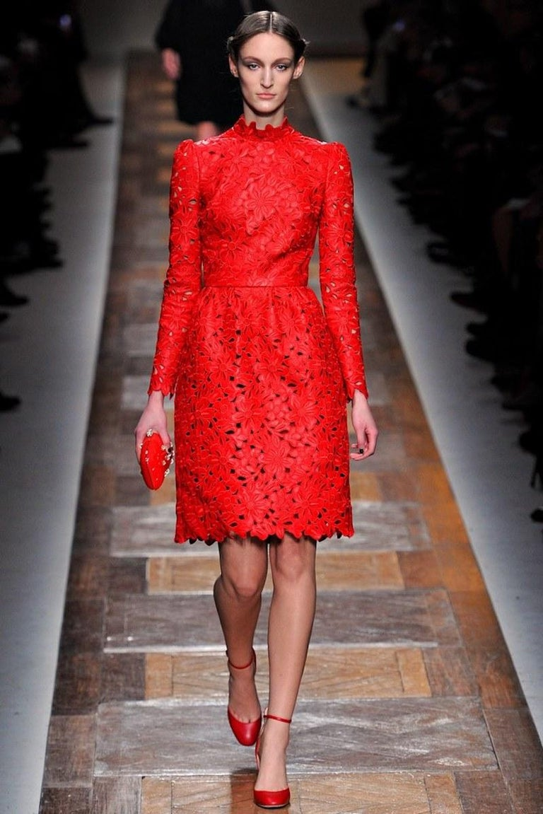 This fabulous Valentino cocktail dress circa Fall 2012 Collection design to commemorate the 50th Anniversary of the Valentino House comes in bold red, floral embroidered, laser cut leather and features a high trim neck, long puff shoulder sleeves,