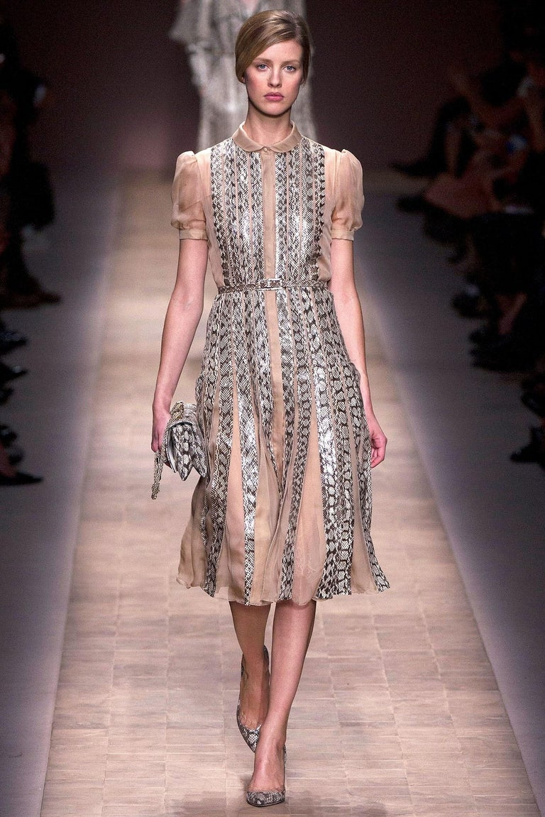 Valentino cocktail dress comes in a peachy beige sheer silk with a round collar, hidden placket button up front, short puff sleeves, fitted drop waist pleated skirt, and snake skin leather stripe overlay throughout. With belt. Spring 2013 Runway.