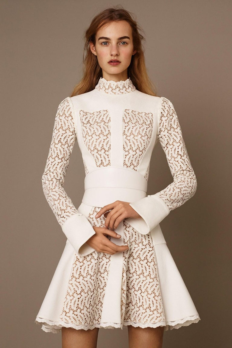 ALEXANDER MCQUEEN Pre-Fall 2015 cocktail dress comes in a cream textured fabric with lace insert panels, high lace stand up collar, long sleeves with folded cuffs, drop waist pleated skirt, and tan beige liner. Belt available separately. Made in