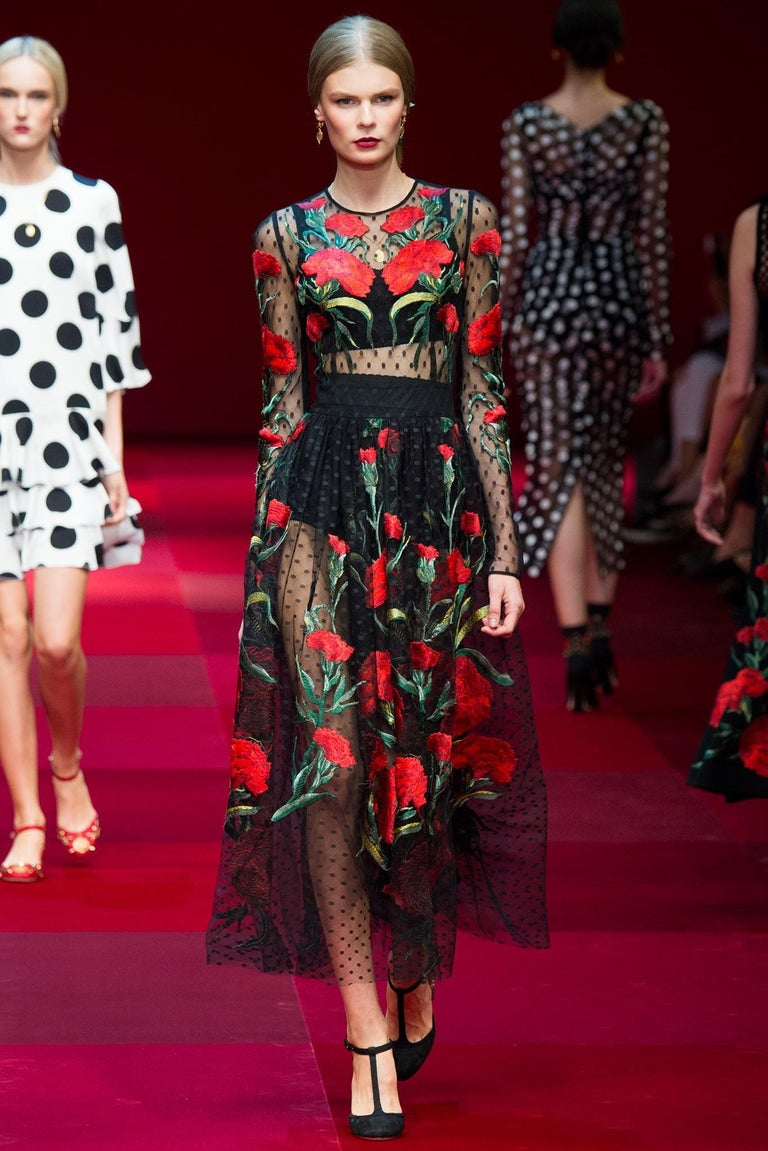 This gorgeous Dolce & Gabbana Spring 2015 collection cropped gown comes in a polka dot tulle lace and features a round neckline, long sleeves, fitted bodice, gathered full skirt, and beautiful red carnations embroidered throughout. Label removed.